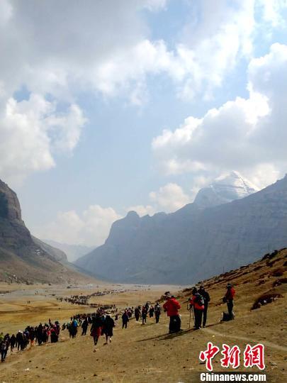 西藏阿里地区独特的自然风光及具有深厚文化底蕴和举世闻名的人文景观,吸引着越来越多的游客走进阿里,旅游业也让当地民众得到越来越多的实惠。图为国内外游客及信众在冈仁波齐神山脚下。 尼玛顿珠 摄