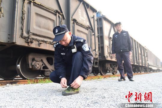 巡视途中,唐楚伟正在给鞋子系鞋带。这样的鞋子,他每年要穿坏4双。 王以照 摄