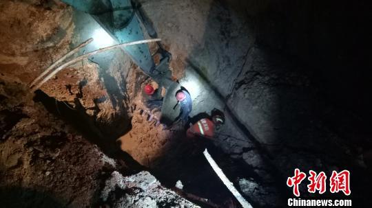 消防员和村民冒着危险继续下井救援。 郑振盛 摄